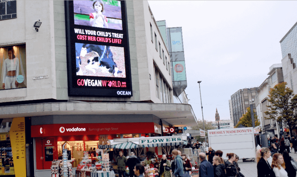 """The image is of a high street.  A large billboard is shown high on the side of a shopping mall.  The illuminated advertisement is in portrait orientation and has two images one above the other.  The top image is of a small child holding an ice cream. The lower image is of a Holstein-Friesian cow licking her newly born baby.  Between the two images are the words: """"Will your child's treat cost her child's life?"""" Below the image of the cow with her calf is the GoVeganWorld.com logo."""