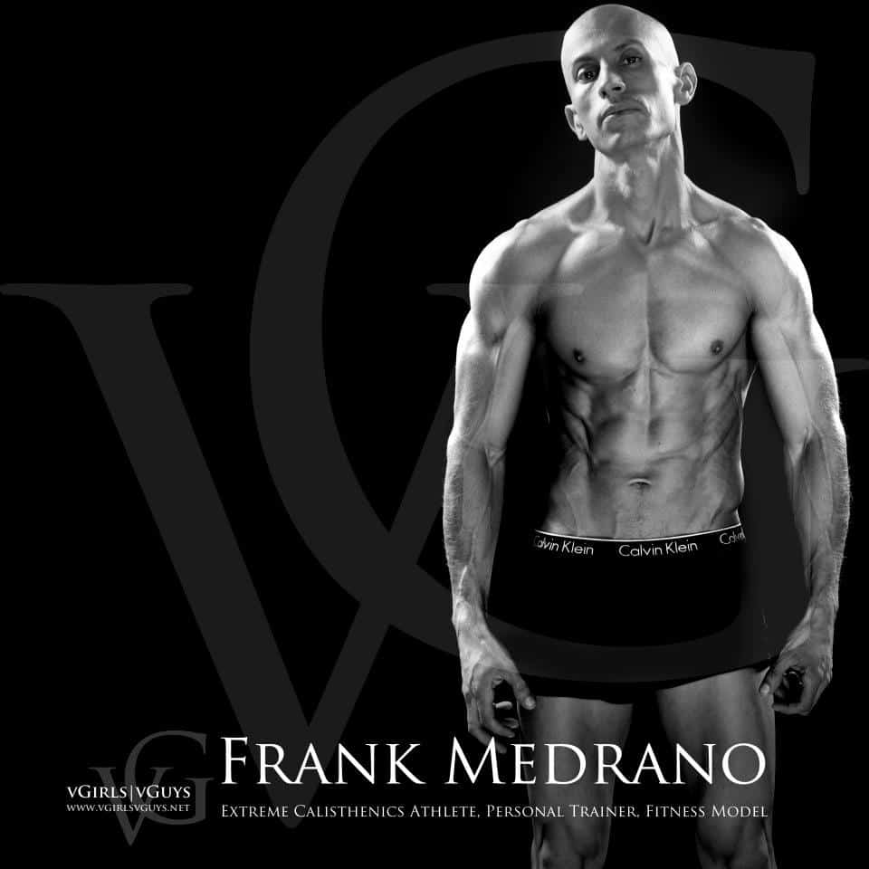 Shirtless Frank Medrano extreme calisthenics athlete, personal trainer and fitness model, standing with arms by his side, on a black background with his name in white lettering