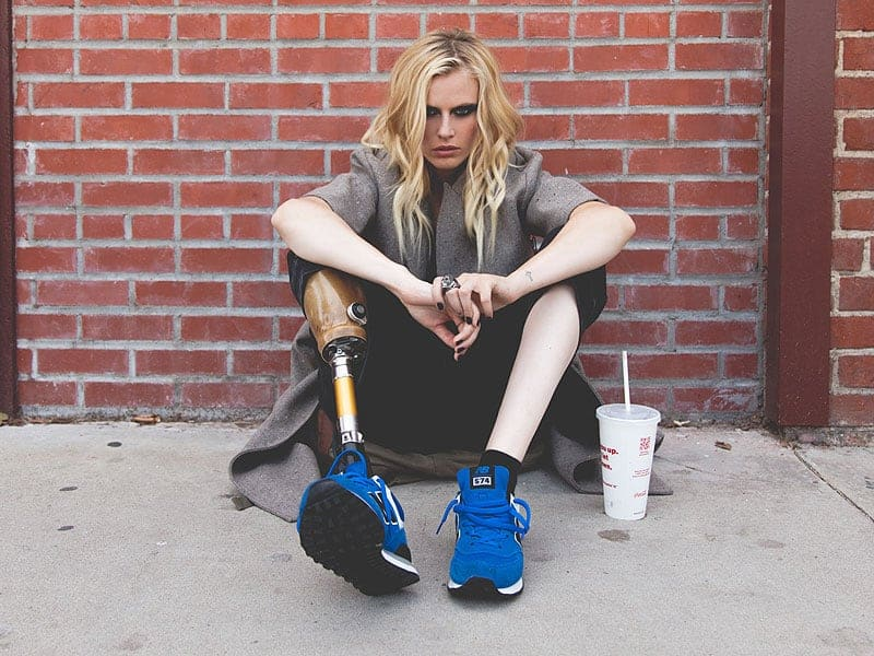 Lauren Wasser, a model who had to have her leg amputated due to toxic shock syndrome from a tampon, sitting on a sidewalk in front of a brick wall with her knees folded up to her chest and her prosthetic lower leg slightly extended.