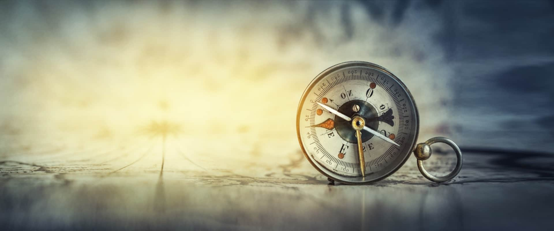 A vintage-style guiding compass standing on edge on top of an out-of-focus aged map.