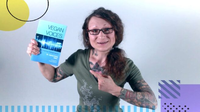 """Emily Moran Barwick, the creator of Bite Size Vegan, holding and enthusiastically pointing to the book """"Vegan Voices: Essays by Inspiring Changemakers""""."""